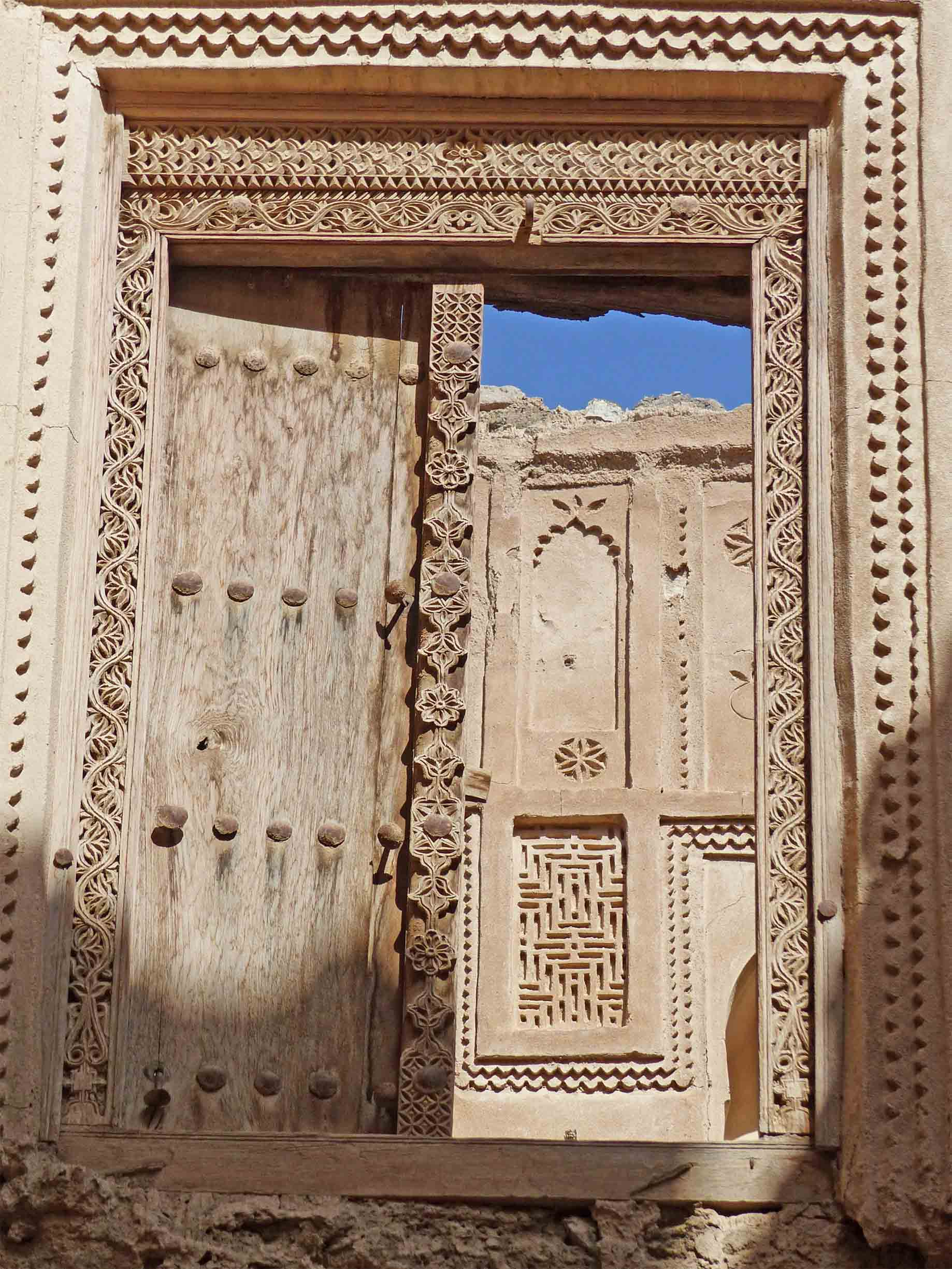 Ornate carved door and frame with carved wall beyond