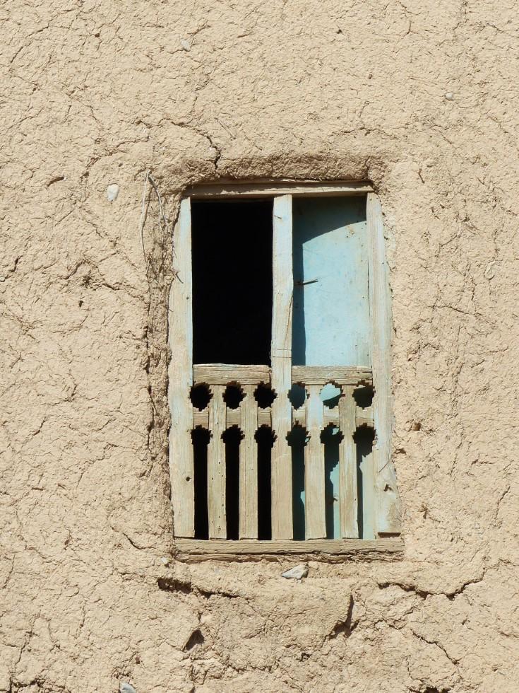 Small shuttered window in adobe wall