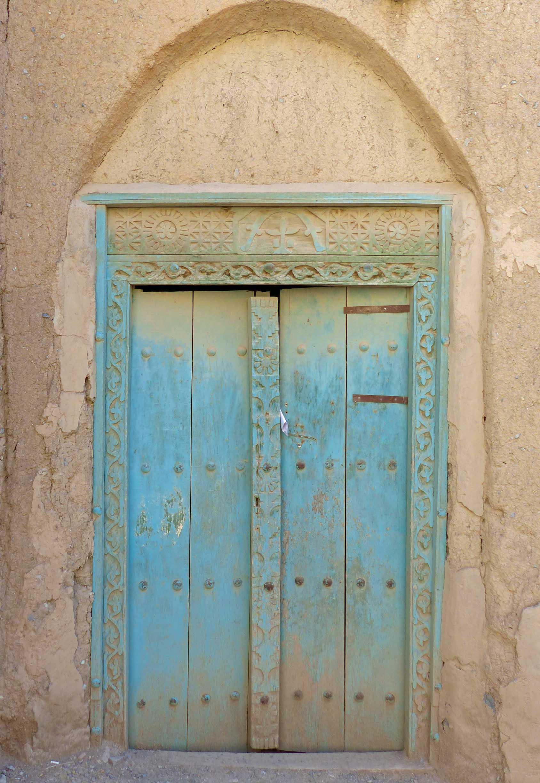 Blue wooden door in adobe wall