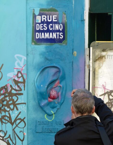 Man photographing a blue painted wall with moulded ear