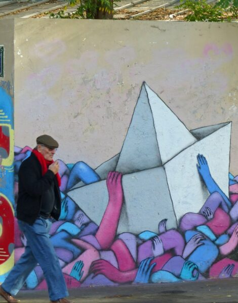 Painting of paper boat with man passing