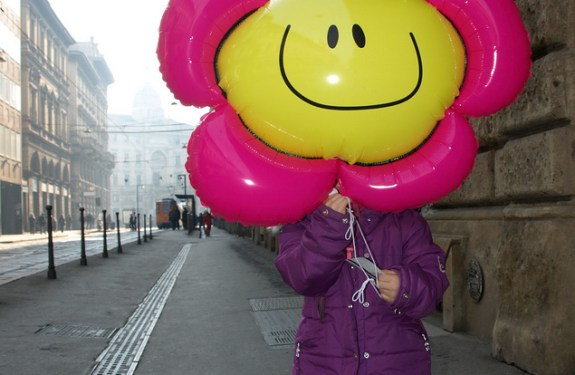 Child hiding behind balloon