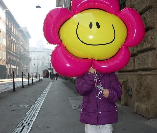 Child hiding behind balloon
