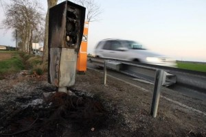 Burn-out: A car speeds by a defunct speed camera on a dual-carriageway in Brittany