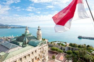 View from above: the Hôtel de Paris beneath the flag of Monaco with the Mediterranean Sea in the background