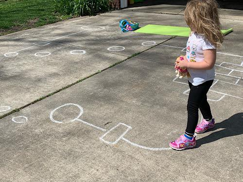 A 3 year old doing a sidewalk chalk obstacle course