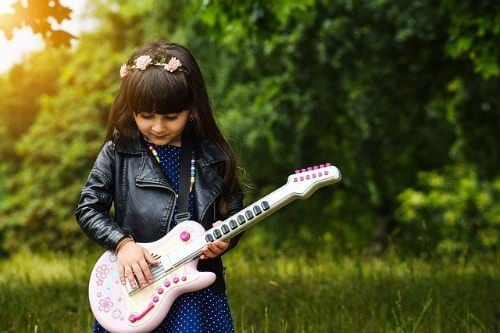 toddler girl pretending to be a rock star