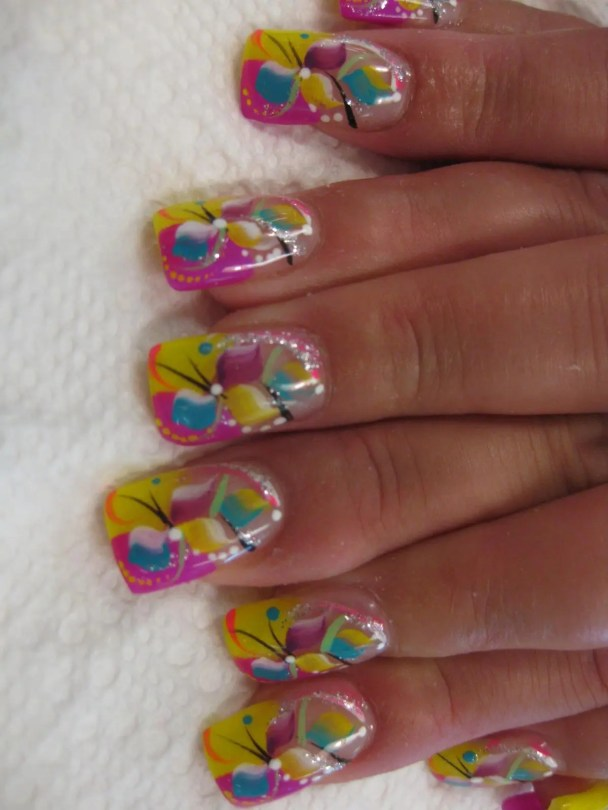 Bright pink and yellow tips with bright colored pastel flower over the top and yellow, white, sparkly swirls
