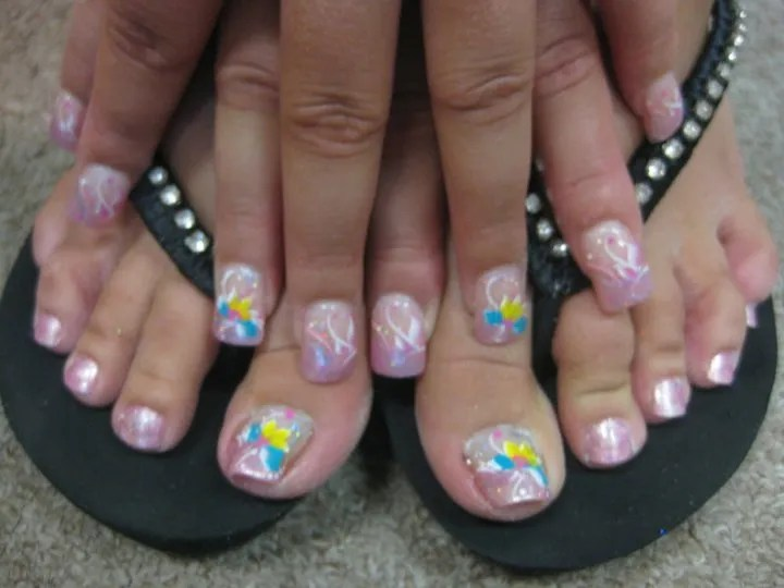 Sparkling pink tip with pink/white swirls topped with sky blue/bright yellow and pink flower petals, white swirls, and sparkles.