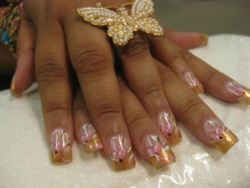 Sparkling champagne colored tip with light pink/white lilies, black dots and white/pink/black swirls.