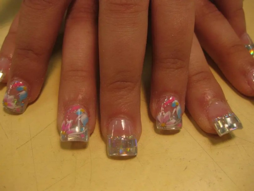 Sparkling silver tip with pink flower petals, white swirls, yellow/pink/blue dots topped with sky blue/white petals, pink swirl, white dots.