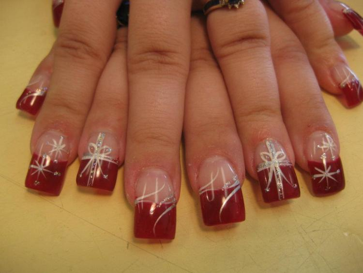 Christmas red tip topped by flesh colored nail with white/sparkling Christmas present bow and sparkle clusters.