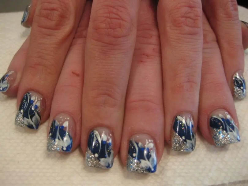 Angled sparkling silver tip below angled sparkling sapphire blue band topped with thiw lily petals, white swirls, bright blue/white dots.