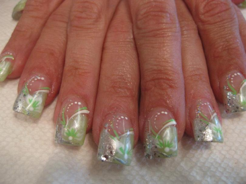 Half curved sparkling silver/half curved translucent green tip, green/white flower, green/white swirls, white dots.