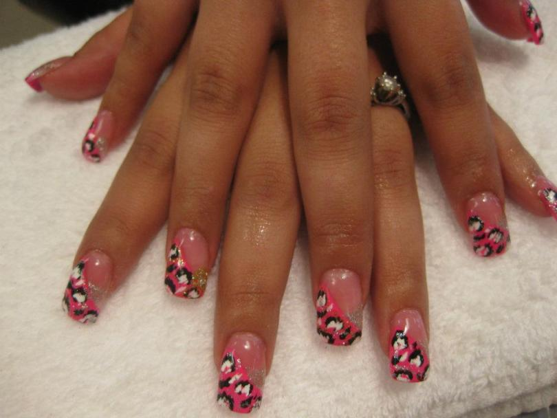 Steeply angled bright pink tip with white/black leopard spots and sparkly clusters.