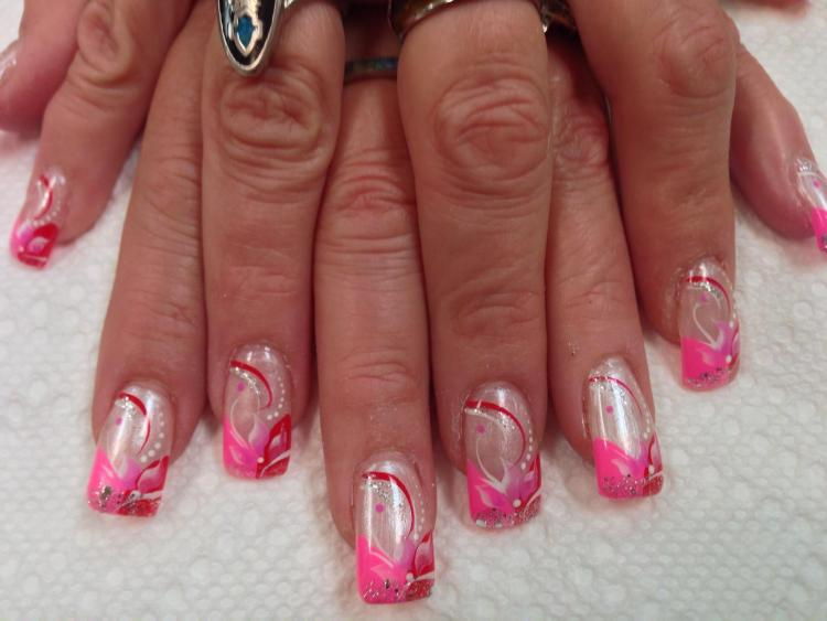 Half curved bright pink/half curved red tip on translucent nail with pink/white lily, red/white/sparkly swirls, shite/pink dots.