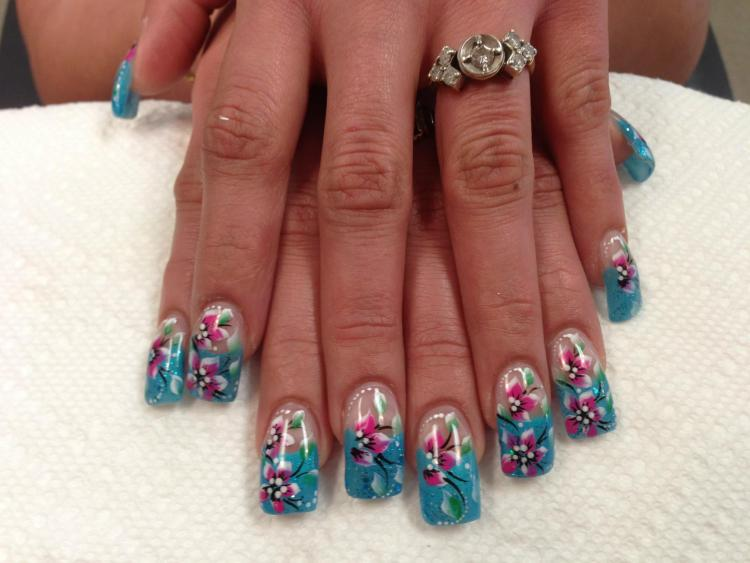 Sparkly aqua blue tip with pink/white calla lily (or lilies), green/white swishes, black swirls, white dots.