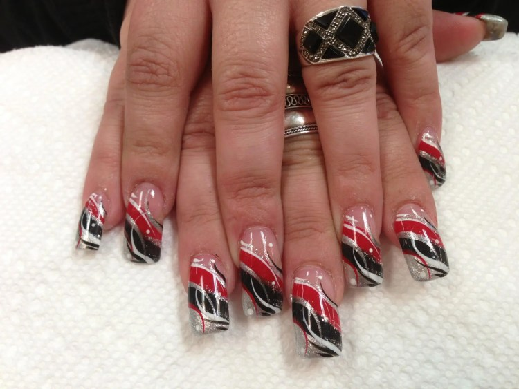 Angled sparkling silver tip under angled black and red bands, red/white/black/silver swirls, white dots.