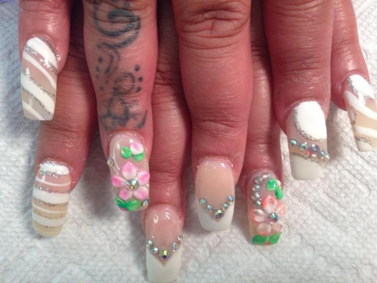 V-shaped opaque white tip with diamond glue-ons OR translucent nail with 3D pink/green daisy and diamond glue-ons