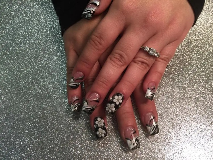 Black nail with two 3D white flowers/silver centers, sparkly swirls AND angled black/white tips with white/black/silver/sparkly swirls.