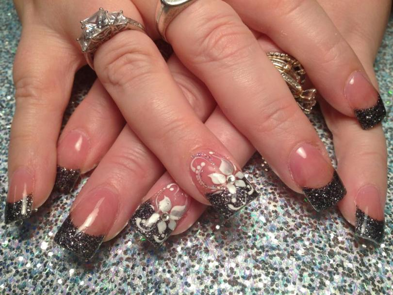 Sparkly black tip with white/silver lily, diamond glue-on center, white/sparkly swirls, white dots.