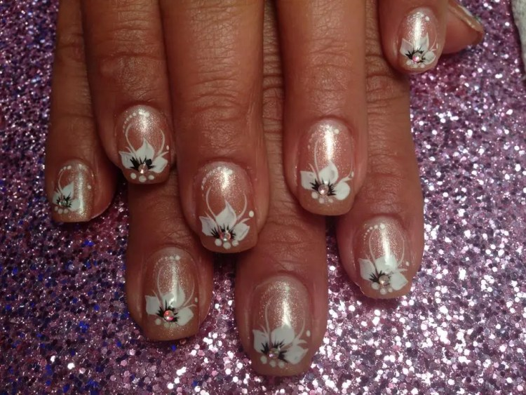 Sparkly champagne nail with white lily, diamond glue-on center, white swirls, white dots.