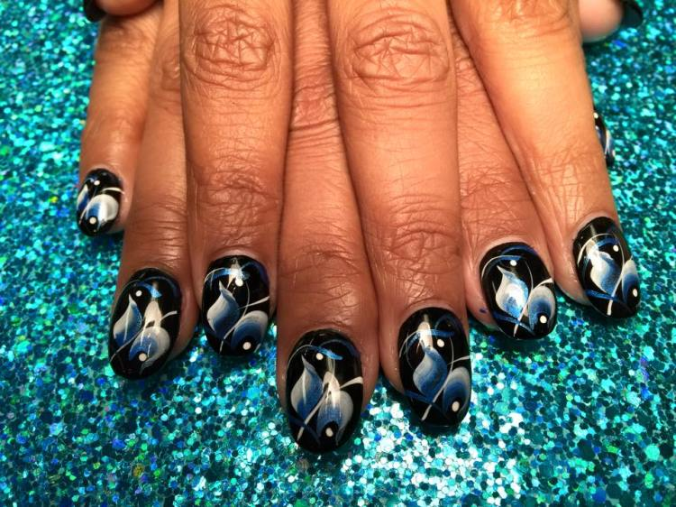 Shiny Black onyx nail with sky blue/white swishes, white/shiny blue swirls, white dots.