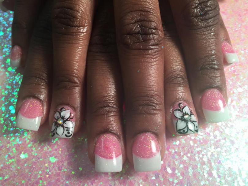 Opaque brilliant white tip, sparkly pink nail with black-outlined white flower, diamond glue-on center, black swirls, white dots.