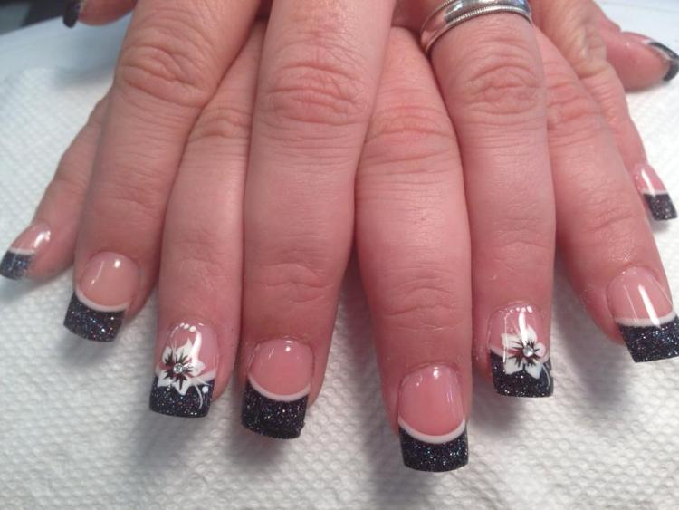 Sparkly black tip with thin crescent moon line above, flesh colored nail, White stargazer lily, diamond glue-on, white dots/swirls.