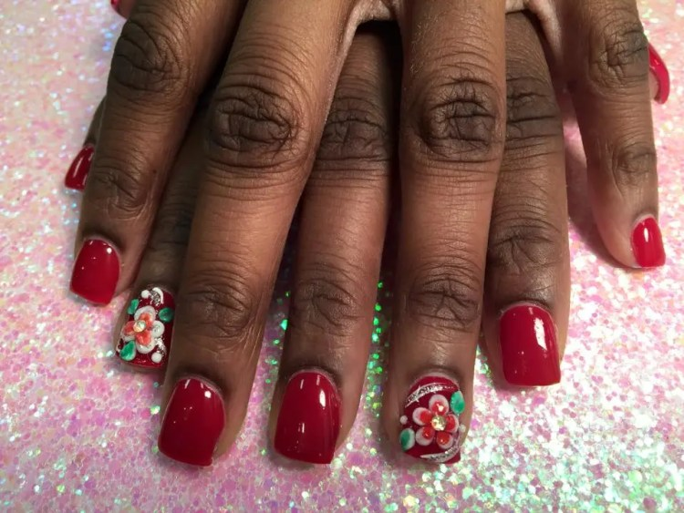 Brilliant red nail with raised 3D orange/white lily, raised 3D green petals, sparkles, white swirls.