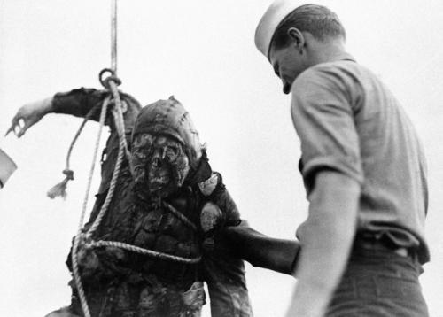 Американский моряк смотрит на обгоревший труп японского пилота, который достали со дна Перл-Харбор