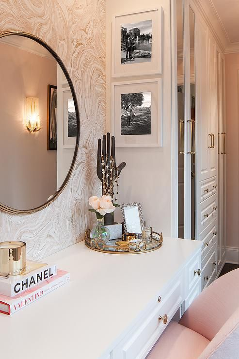 Glam dressing room boasts a blush pink upholstered chair placed before a white m...