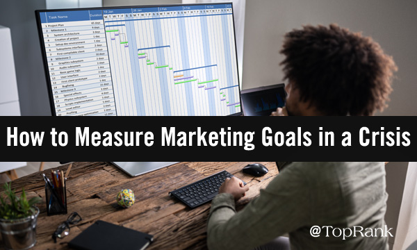 Seated man looking a monitor of marketing goals.