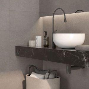 Grijze betonlook tegels in combinatie met een donker bruin marmeren werkblad.