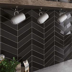 Een spatwand met zwarte chevron tegels. Hier combineren matte en blinkende wandtegels.