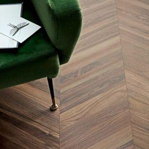 Een legpatroon in donker eik bruine houtlook tegels. Hier geplaatst in visgraat