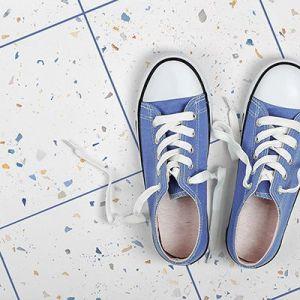 Witte keramische granito tegels met felle terrazzo fragmenten. Opgevoegd in fel blauw mapei ultracolor plus voegsel.