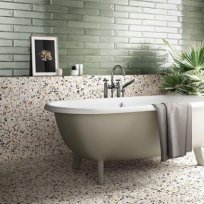 badkamer vloer met witte terrazzo met felle kleuren in formaat 20x20cm gecombineerd met groen langwerpige wandtegels voor de badkamerwand.