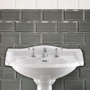 Gijze metrotegels in de badkamer. Afgewerkt met een boord met metrotegels wit.