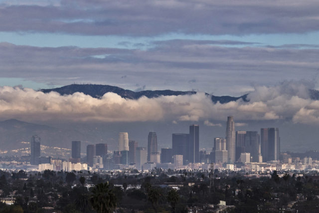 The San Gabriel Mountains are seen in the background during cloud cover over the Los Angeles skyline