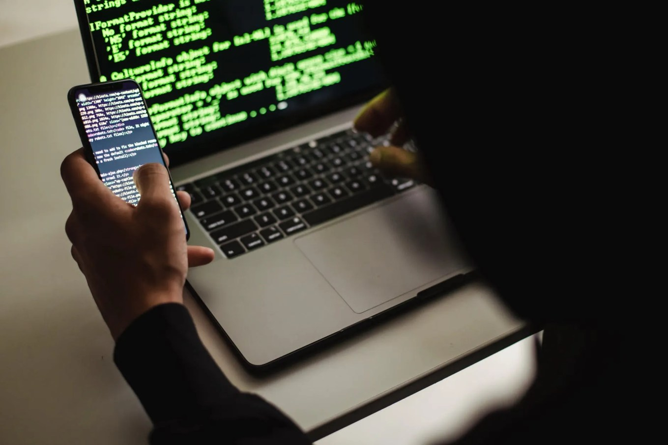 crop unrecognizable developer using laptop and smartphone