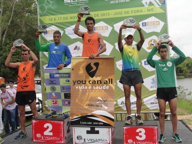 Flávio levanta o troféu no topo do pódio no meio dos outros vencedores da prova.(Foto: Toque de Bola)