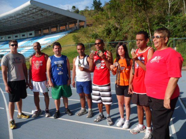 Atletas e equipe do JF Paralímpico com medalhas em treino na UFJF. (Foto: Gedair Reis)