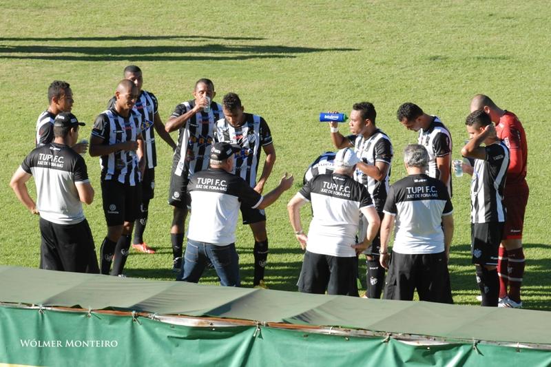 Paulo Campos conversa com os jogadores do Tupi em parada para  hidratação durante jogo contra o Guarani