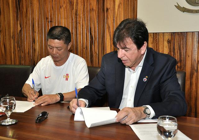 Vice-presidente da Federação Chinesa de Atletismo, FengShu Young e reitor da UFJF, Henrique Duque, assinam documento oficializando acerto