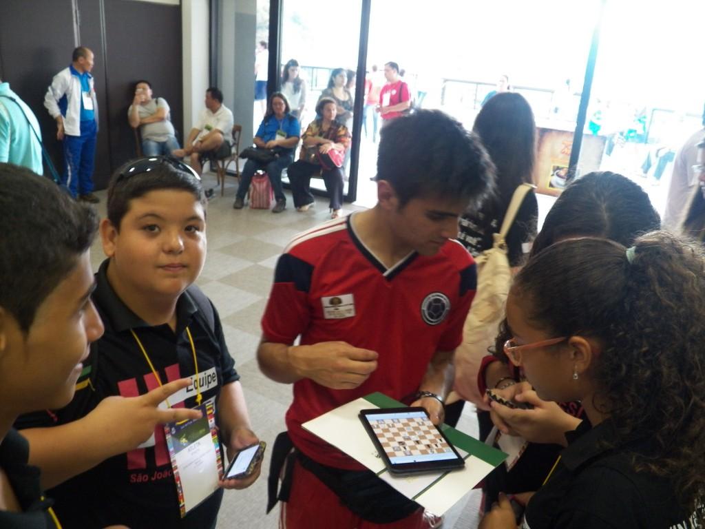 Jovens brasileiros jogam, no tablet, xadrez com atleta da Colômbia