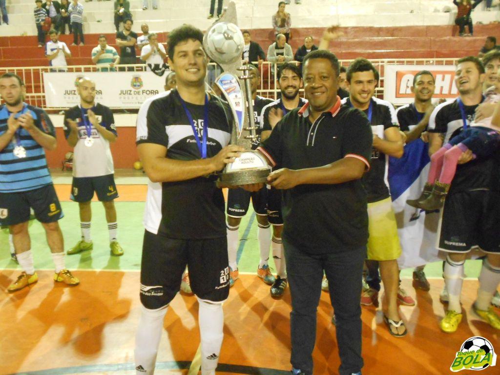 Secretário de Esporte e Lazer, pastor Carlos Bonifácio premia o capitão do 2010, Bruno, com a taça de campeão.
