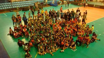Dezenas de crianças reunidas em torno do basquete no ginásio da Faefid-UFJF