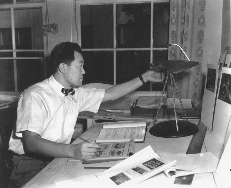 Paramount unit art director Albert Nozaki in 1951, sketching some of the continuity drawings for George Pal's adaptation of The War of the Worlds.  For reference, Nozaki used a copper and Lucite prototype of the Martian war machine constructed by the Paramount prop department from his original drawings.  In this later stage of the machine's evolution, all the essential details of its design have been resolved except for the positioning of the cobra head-shaped heat ray.  The heat ray was finally placed slightly forward of center instead of at the rear as shown in this photograph. Click to enlarge.