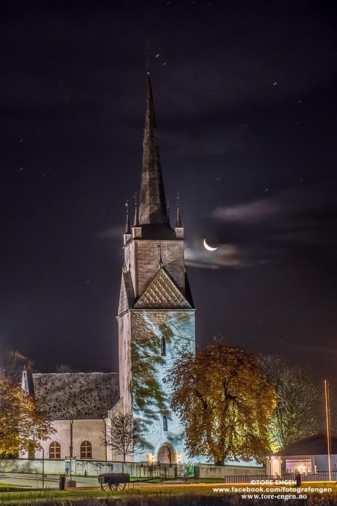 En måneskalk og stjernehimmel over Nes kirke, Ringsaker by night